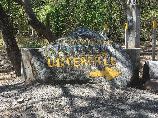The waterfall entrance is marked with a large rock.
