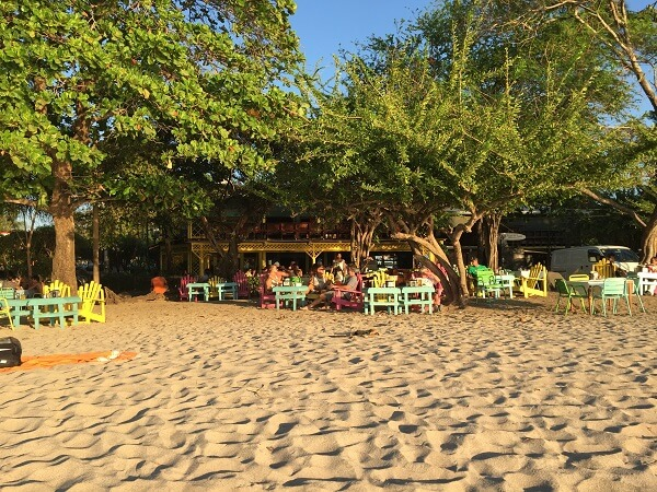 Tables and chairs in the sand right next to the water at the Pacifico bar in Tamarindo